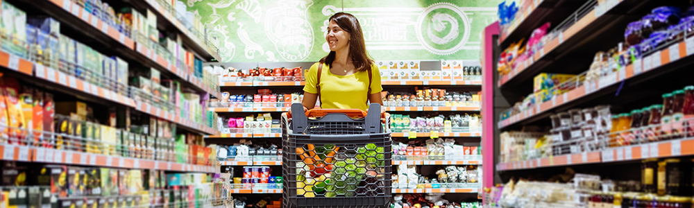 mladá žena s nákupním vozíkem v obchodě s potravinami, což znamená pozor na vyprodání zásob.